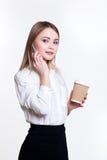 白色背景的年轻可爱的企业女孩用咖啡和电话 库存图片