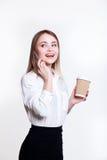 白色背景的年轻可爱的企业女孩用咖啡和电话 图库摄影