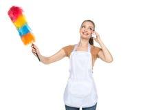 白色背景的年轻主妇清洁房子 库存照片