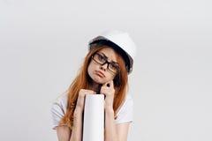 白色背景的年轻美丽的女性工程师拿着图纸,建筑,设计师 免版税库存照片
