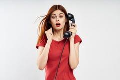 白色背景的年轻美丽的妇女在红色礼服拿着输送路线电话,情感 库存照片