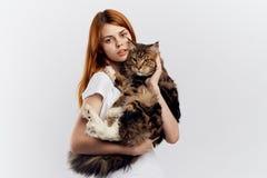 白色背景的年轻美丽的妇女拿着一只猫,宠物,动物,女孩 免版税库存照片