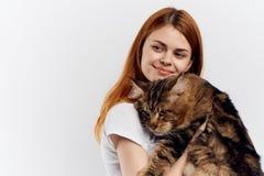 白色背景的年轻美丽的妇女拿着一只猫,宠物,情感 免版税库存照片