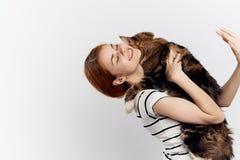 白色背景的年轻美丽的妇女拿着一只猫,宠物 免版税库存图片