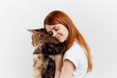 白色背景的年轻美丽的妇女拿着一只猫,微笑,宠物 图库摄影