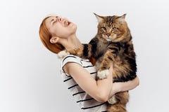 白色背景的年轻美丽的妇女拿着一只猫,过敏 免版税库存照片