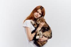 白色背景的年轻美丽的妇女拿着一只猫 库存图片