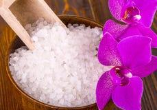 白色腌制槽用食盐和一个袋子与Orhid木表面上 图库摄影