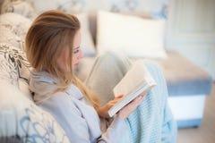 白色舒适床和一个美丽的女孩,读一本家的书在晚上,概念和舒适 关闭 免版税库存图片