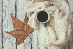 白色舒适被编织的毛线衣的顶视图图象有到咖啡的和秋天叶子在一张木桌上 库存图片