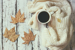 白色舒适被编织的毛线衣的顶视图图象有到咖啡的和秋天叶子在一张木桌上 免版税库存图片