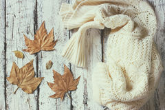 白色舒适被编织的毛线衣的顶视图图象有秋天干燥叶子的在一张木桌上 退色的减速火箭的样式图象 库存图片