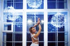 白色舞蹈紧身连衣裤和Pointe鞋子的,跳芭蕾舞者年轻美丽的女孩 反对窗口,样式,雍容 免版税库存图片