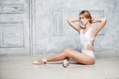 白色舞蹈紧身连衣裤和Pointe鞋子的,跳芭蕾舞者年轻美丽的女孩 库存照片
