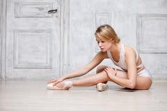 白色舞蹈紧身连衣裤和Pointe鞋子的,跳芭蕾舞者年轻美丽的女孩 免版税库存图片
