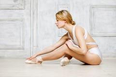 白色舞蹈紧身连衣裤和Pointe鞋子的,跳芭蕾舞者年轻美丽的女孩 图库摄影