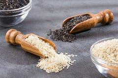 白色芝麻和黑芝麻籽-热带香草indicum 木背景 免版税库存图片