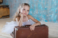 白色芭蕾舞短裙的小可爱的芭蕾舞女演员有老葡萄酒suitcas的 免版税库存照片