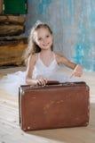白色芭蕾舞短裙的小可爱的芭蕾舞女演员有老葡萄酒suitcas的 库存照片