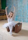 白色芭蕾舞短裙的小可爱的芭蕾舞女演员有老葡萄酒suitcas的 库存图片