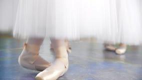 白色芭蕾舞短裙的芭蕾舞女演员在pointe鞋子弹起在演播室 股票视频