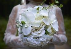 白色花束由白色礼服的妇女举行了在森林里 库存照片