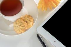 白色茶与数字式片剂的在简单的workpl 免版税库存照片