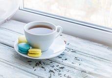 白色茶和macarons在窗口附近 图库摄影