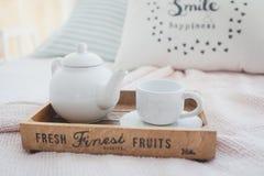 白色茶壶和杯子在一个木盘子 库存图片