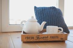白色茶壶和杯子在一个木盘子 库存照片
