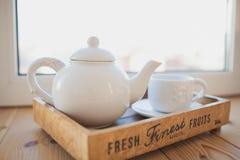白色茶壶和杯子在一个木盘子 免版税库存图片