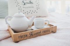 白色茶壶和杯子在一个木盘子 免版税图库摄影