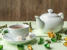 白色茶壶和杯子用茶 免版税图库摄影