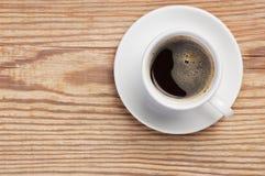 白色茶碟和咖啡与泡沫的在土气木与空间的桌背景顶视图文本的 库存照片