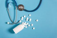 白色药片、瓶和听诊器在蓝色背景,顶视图 医学医疗保健药房概念 库存照片
