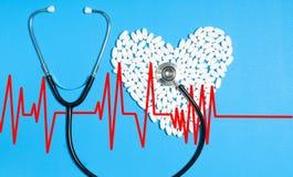 白色药片和听诊器的心脏在蓝色背景 库存图片