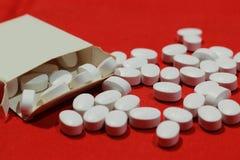 白色药片和小包堆有红色背景 免版税库存照片