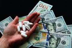 白色药片在手中和dolary在黑背景 很多荧光的药片 库存图片