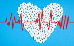 白色药片的心脏在蓝色背景的 库存照片