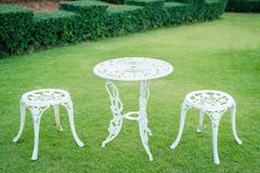 白色葡萄酒椅子在庭院里 免版税库存图片
