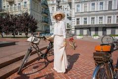 白色葡萄酒衣物的美丽的妇女准备好循环在老自行车在时尚节日减速火箭的巡航 库存图片