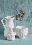 白色葡萄酒陶器-上釉的水罐、陶瓷碗和白陶瓷圣诞老人蓝色木表面上 免版税库存图片