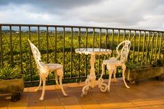 白色葡萄酒锻铁从事园艺的家具、套空的圆桌和在阳台的两把典雅的椅子 免版税库存照片