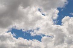 白色蓬松风雨如磐的云彩后面明亮地点燃了,蓝天 免版税库存照片