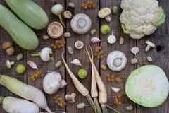 白色蔬菜和水果在木背景 平的位置 无核小葡萄干,花椰菜,蘑菇,萝卜,荷兰芹,采蘑菇大蒜 免版税图库摄影