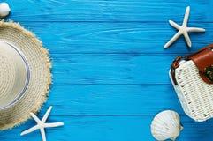 白色藤条袋子,在蓝色背景的草帽 竹时髦袋子,海星,壳 夏天时尚舱内甲板放置,假期,旅行 库存图片