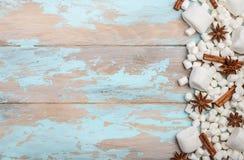 白色蛋白软糖和冬天香料在蓝色木背景 库存图片