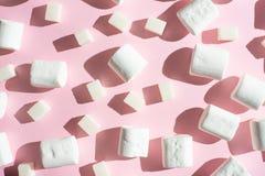 白色蛋白软糖,与糖立方体,在桃红色背景,与坚硬阴影 能力使用作为背景,概念  图库摄影