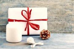 白色蜡烛、圣诞礼物和小中看不中用的物品 免版税库存照片