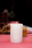 白色蜡烛在桌上站立 与蜡烛的欢乐构成 对光检查圣诞节装饰表包裹 一个美好的桌设置 库存照片